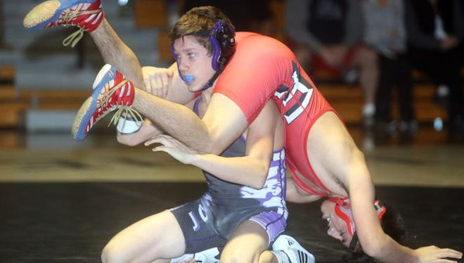 Matthew Kramer of John Jay Cross River, in purple, defeated Amos Rivera of Fox Lane in a 120 pound bout during a wrestling meet at John Jay High School Dec. 8, 2015.