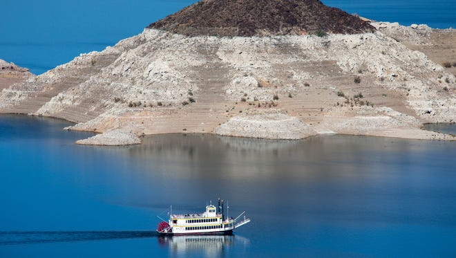 """The Desert Princess, a three-level paddle-wheeler, passes Rock Island, November 17, 2014, while leaving Hemenway Harbor on it mid-day sightseeing cruse.  A high-water mark or """"bathtub ring"""" is visible on the shoreline; Lake Mead is down over 145 vertical feet."""