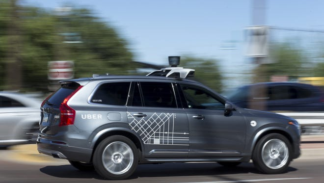 An Uber vehicle cruises in Tempe, Aug. 25, 2017, near Mill Avenue and Rio Salado Parkway.