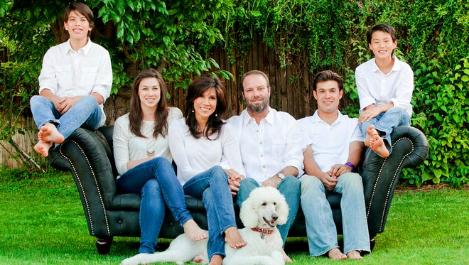 (L-R) Seamus, Wen, Lin Sue, Sean, Taylor and Zachary Cooney, and their dog, Max.