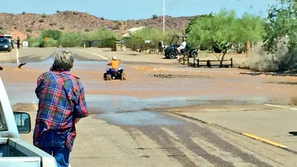 A child on an ATV tried to cross a flooded road in North Surprise.