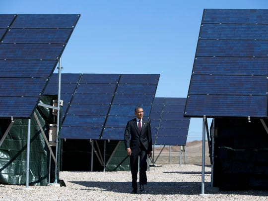 President Barack Obama walks through a solar farm at
