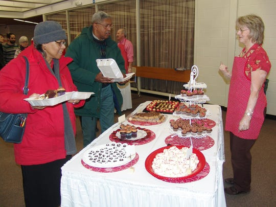 Norma Owens, right, helps Gloria and William Johnson make their selections from the sweet treats table at a past Chocolate Extravaganza in this Tribune file photo.