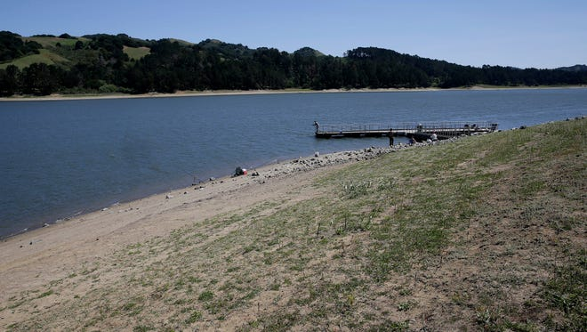 A man fishes off a pier at San Pablo Reservoir Recreation Area in El Sobrante, Calif., on Thursday, April 2, 2015. A spokeswoman for the East Bay Municipal Utility District said the reservoir is about half full.