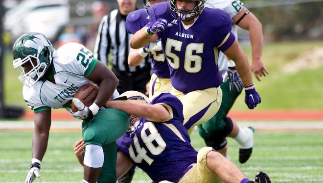 Albion College defensive lineman Dillon Ervin wraps up running back Anfernee Roberts of Illinois Wesleyan on Saturday at Sprankle-Sprandel Stadium in Albion.