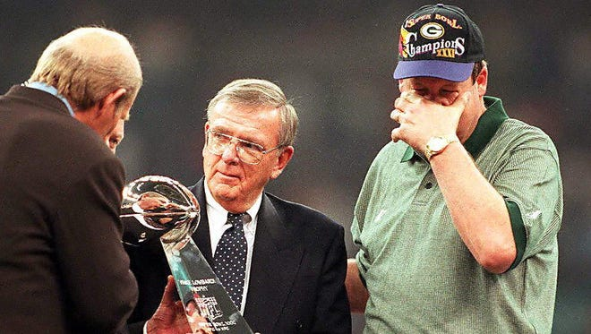 Green Bay Packers coach Mike Holmgren (right) wipes his eyes as Packers general manager Ron Wolf (center) receives the Vince Lombardi Trophy after Green Bay won Super Bowl XXXI.