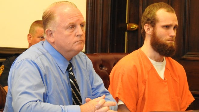 Justin A. Wright, seated next to attorney Jeff Mullen, reacts to being sentenced Tuesday in Coshocton County Common Pleas Court.