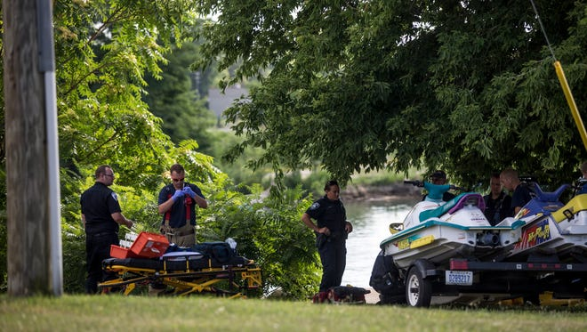 Members of the Port Huron Fire Department and Tri-Hospital EMS tend to a man that was run over by their vehicle as it rolled down a hill Tuesday, July 26, 2016 where Mc Pherson Street dead ends at the Black River.