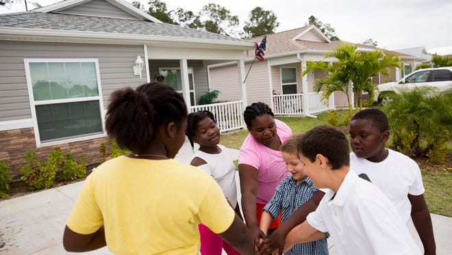 Neighborhood children Fabiana Jean-Baptiste, 9, from left; Leoneyika Cetlute, 10; Fedena Brutus, 11; Sevrin Evans, 8; his brother Mikael, 12; and Felix Brutus, 9, all of whom live in the Legacy Lakes community, play outside Tuesday, April 11, 2017, in North Naples. The community of 55 homes, built by Habitat for Humanity of Collier County, allows families to afford a new home after a rigorous application process in a safe neighborhood.