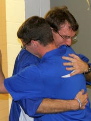 Horeseheads coach Mark Miles (front) hugs Horseheads teacher Brendan McCarthy after the Blue Raiders won the Section 4 Class A girls swimming title in November of 2013.