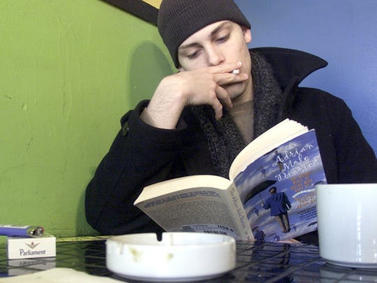 "Chadwick Moore, then a student at the University of Iowa, is shown at the Tobacco Bowl in downtown Iowa City in January 2004. He's reading ""The Adrian Mole Diaries."""