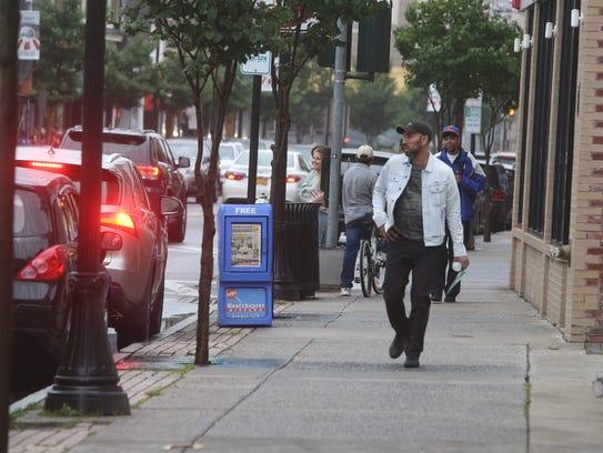 Pedestrians walk along Main St. in Port Chester July