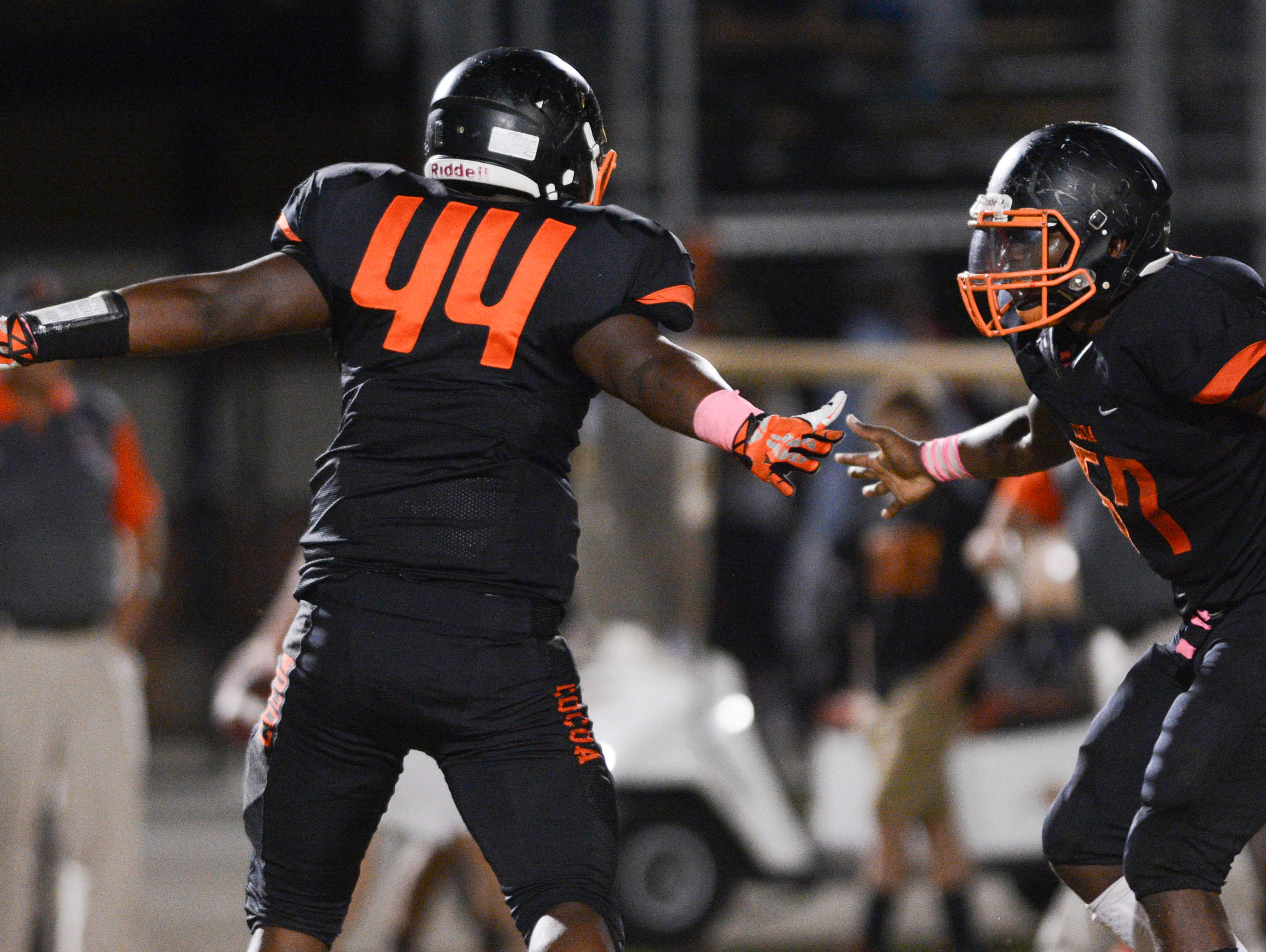 Howard Stewart of Cocoa gets congratulated by teammate Eddie Ware after he made a sack in Friday's game.