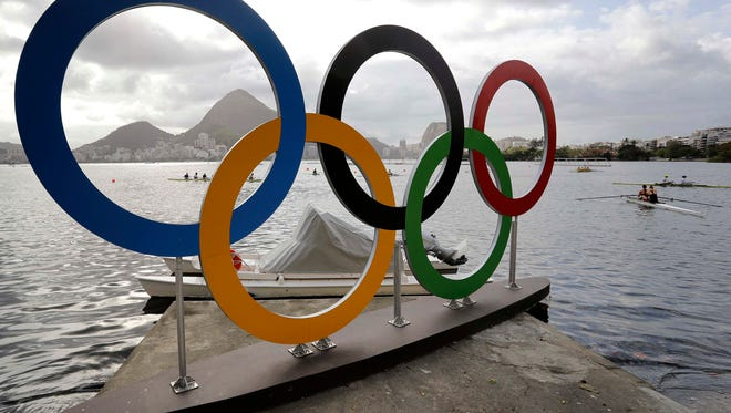 Athletes warm up during rowing team practices near the Olympic rings in Lagoa ahead of the 2016 Summer Olympics in Rio de Janeiro, Brazil, Wednesday.