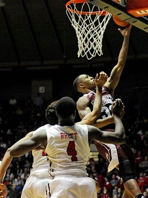 Mississippi State guard Craig Sword (32) shoots past Ole Miss forward Sebastian Saiz (11) and forward M.J. Rhett (4) during the second half of an NCAA college basketball game in Oxford, Miss., Wednesday, Jan. 28, 2015. Mississippi won 79-73. (AP Photo/Thomas Graning)