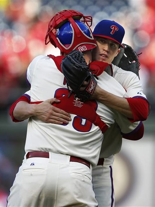 Philadelphia Phillies pitcher Ken Giles (53) hugs catcher Cameron Rupp (29) after getting the final out in the ninth inning against the Miami Marlins on Sunday in Philadelphia. The Phillies defeated the Marlins 7-2 to avoid losing 100 games this season.
