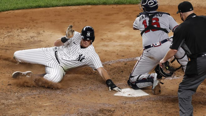 New York Yankees DJ LeMahieu, left, scores on Aaron Hick's fourth-inning double as Atlanta Braves catcher Travis d'Arnaud, center, waits for the throw in a baseball game, Wednesday, Aug. 12, 2020, in New York. Home plate umpire Todd Tichenor watches the play at right.