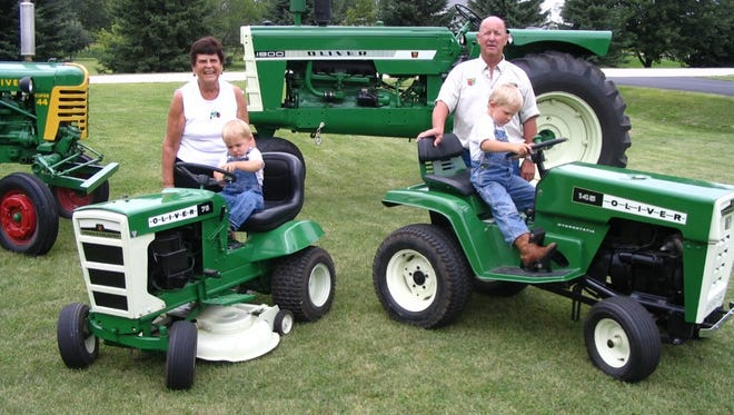 Gloria Twohig, standing left, with grandson Carter Twohig, almost 2, and Jim Twohig, standing right, with grandson Colin Twohig, 4, are seated on Oliver lawnmowers that will be at the Steam & Gas Engine Show Sept. 13-14 in Calumetville. The Twohigs Super 44, left, and 1800 Oliver tractors are in the background.
