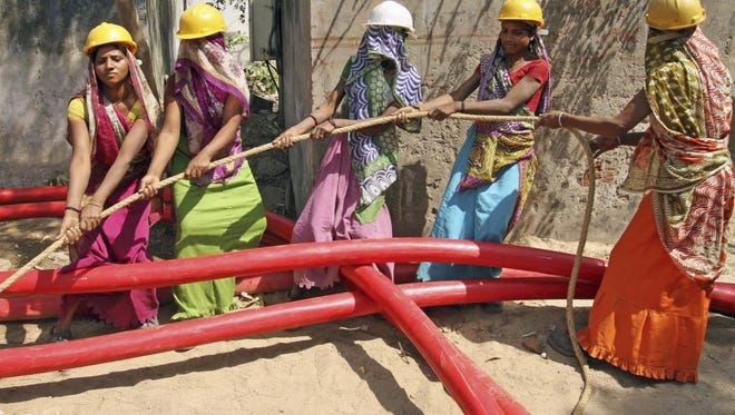 Indian women laborers lay a cable for an electricity company in Ahmadabad last year.