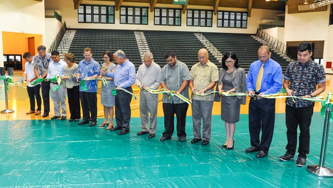 University of Guam President Robert Underwood, center, and other officials take part in a ribbon cutting ceremony to celebrate the renovations completed in the main arena of the Calvo Field House on Oct. 8. Work performed during the renovation included the refinishing of the 24,000-square-foot wood floor; installation of a new, automated bleacher system, energy-efficient air conditioning system, a new floor covering system, new window shades, ADA-compliant railing systems and new doors, according to Jonas Macapinlac, UOG Integrated Marketing Communications director.
