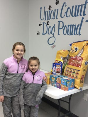 Cortlyn and Ainsley Elder with their supplies donated to the UC Dog Pound.