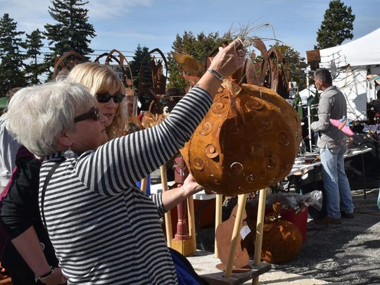 Penny Botcher of Oconomowoc looks over a laser-cut metal pumpkin from Aster Park Floral of Green Bay in the arts and crafts show at a past Pumpkin Patch in Egg Harbor.