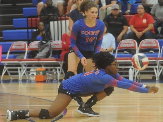 Cooper's Daniece Edwards digs a Lubbock Coronado shot while Cheyenne Sherwood looks on.