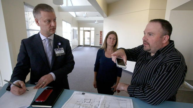 Brent DeMoe, right, with Polk County Family & Community Outreach, talks with Phillip Armstrong and Karen Remington, both of Salem Health, on Friday, March 6 , 2015, in Independence, Ore. Polk County is creating a school based health center that will provide medical, dental and mental health services to not only students, but other members of the community.