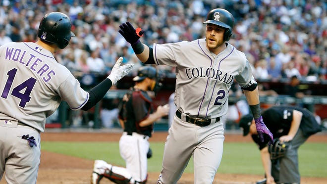 Colorado Rockies' Trevor Story (27) is congratulated by teammate Tony Wolters (14) after hitting a solo home run against the Arizona Diamondbacks during the third inning of a baseball game, Saturday, April 29, 2017, in Phoenix. (AP Photo/Ralph Freso)