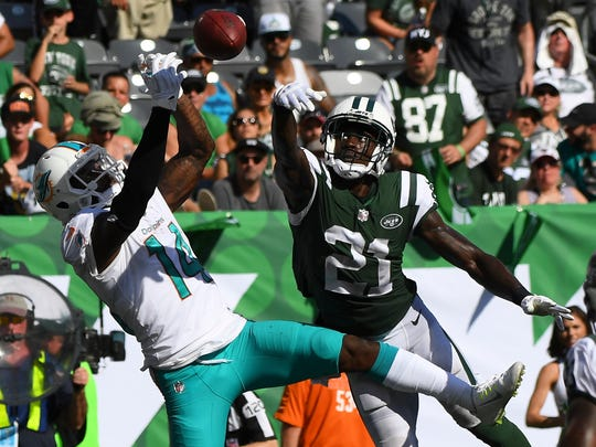 New York Jets cornerback Morris Claiborne (21) breaks up a touchdown attempt to Miami Dolphins wide receiver Jarvis Landry (14) in the second half  at MetLife Stadium.