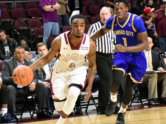 New Mexico State's Ian Baker brings the ball up court