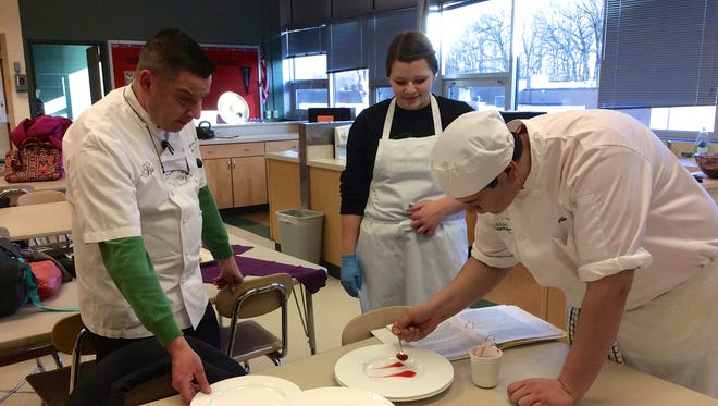 Brian Frakes watches as one of Greendale High School's ProStart team members plates a dish.