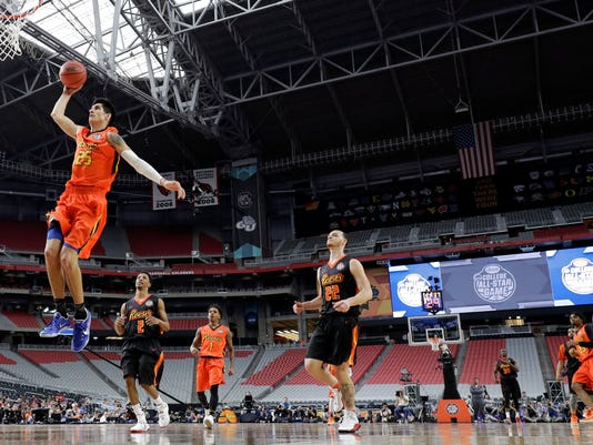 West team's Derek Willis (25) drives to the basket past East team's Reggie Upshaw (22) during the first half of the NCAA All-Star game Friday, March 31, 2017, in Glendale, Ariz. (AP Photo/Mark Humphrey)