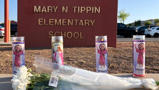 Four religious candles burn by a bouquet of flowers placed in front of Tippin Elementary School at 6541 Bear Ridge in West El Paso Tuesday morning.