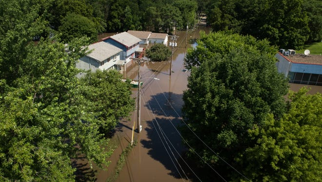 Flood waters spill over Four Mile Creek on Sunday, July 1, 2018 after flash flooding Saturday night in Des Moines.
