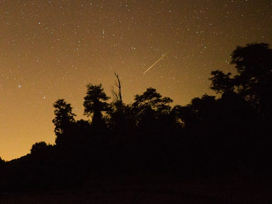 A Perseid meteor arcs over a line of trees in the Shenandoah National Park in the early morning hours of Thursday, Aug. 13, 2015.