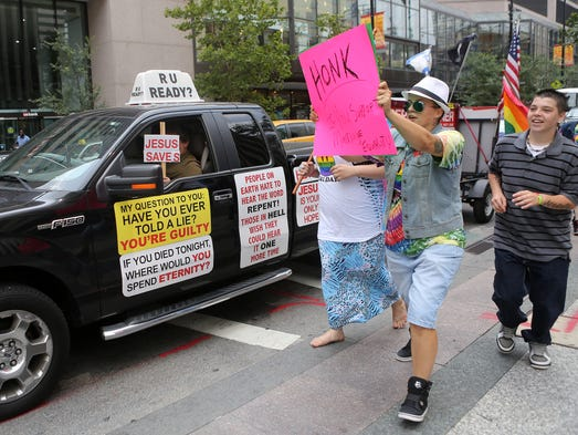 Gay marriage supporters (right) go up against a gay marriage opponent in downtown Cincinnati on Wednesday.