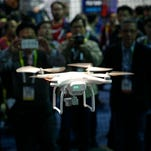 A drone hovers at a booth during CES International in Las Vegas in January. The recent announcement of federal aviation rules specifically designed for small drone aircraft is giving a lift to researchers and a Nevada program set up to foster development of commercial unmanned aerial vehicles.
