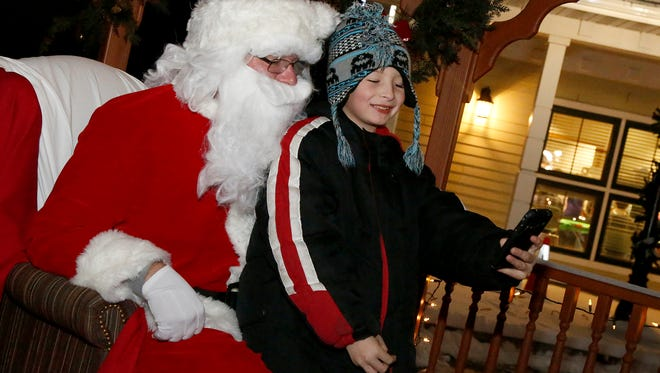 Aiden Spencer, 9, of Elmira, takes a selfie with Santa Dec. 17 at the Big Flats Winter Festival.