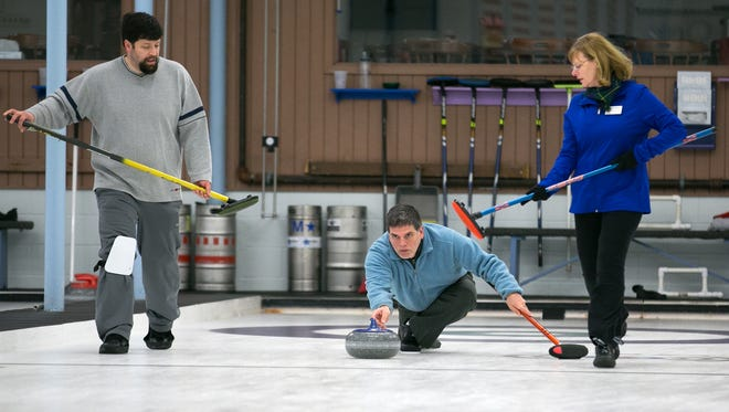 Richard Dimperio plays a shot as Tim Stames and Carol Della Villa assist during a match at Rochester Curling Club on Feb. 8.