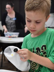 Blake Curry concentrates while sewing a button on his