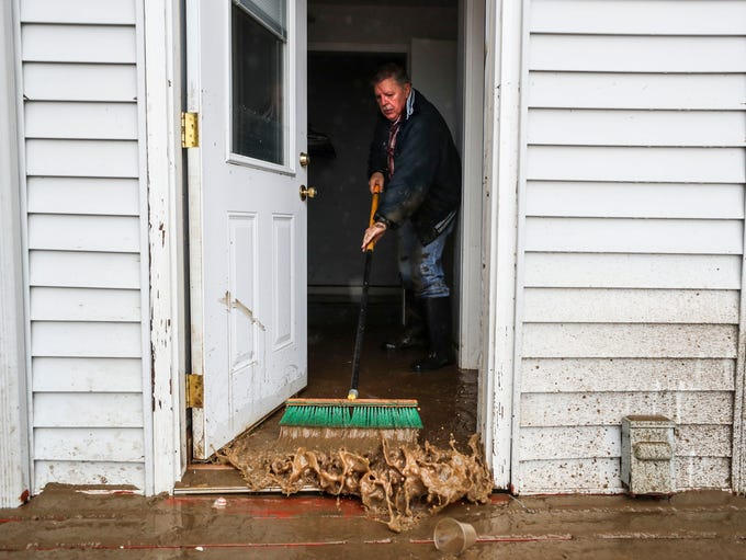 John Skinner uses a broom to push out muddy water from