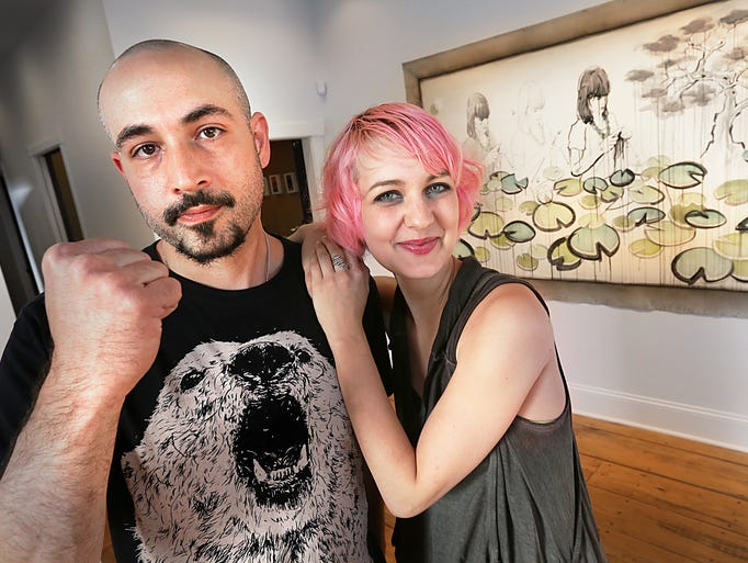 """Artist Justin Cooper (left) and Monster Gallery co-owner Mab Graves pose for a photo during Cooper's closing reception for his """"ANTI-Gravity"""" exhibit.  In the background is one of his show pieces titled """"Lily Thread"""".  Cooper's next exhibit will be in August in the Murphy Art Center with fellow artist Michael Graves."""