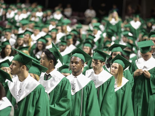 Graduates line up to receive diplomas during the commencement