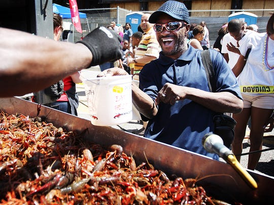 Lionel Maynard jumps back as Charles Banks tries to hand him a live crawfish during the Rajun Cajun Crawfish Festival in 2016. This year's festival is set for April 28.