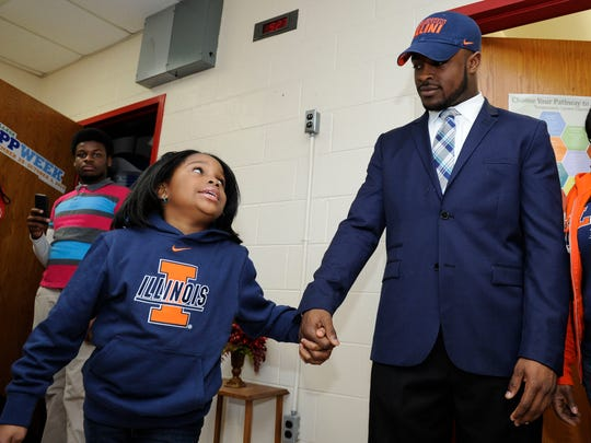 Pearl-Cohn football Ke'Shawn Vaughn holds hands with his sister Sydnee McGee,7, after Vaughn announced he was playing football with University of Illinois during a signing ceremony the the school on Feb. 4, 2015.