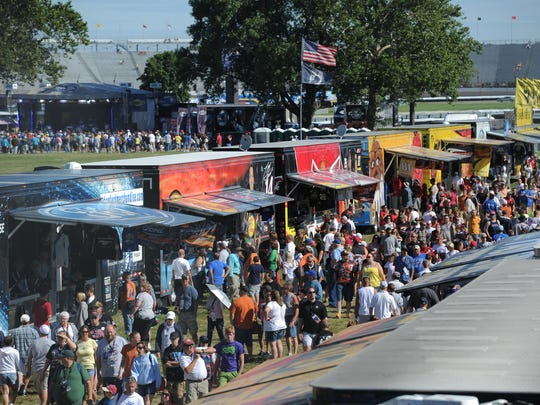 Fans crowd around the many NASCAR team merchandise haulers before the 2013 Brickyard 400 at Indianapolis Motor Speedway.
