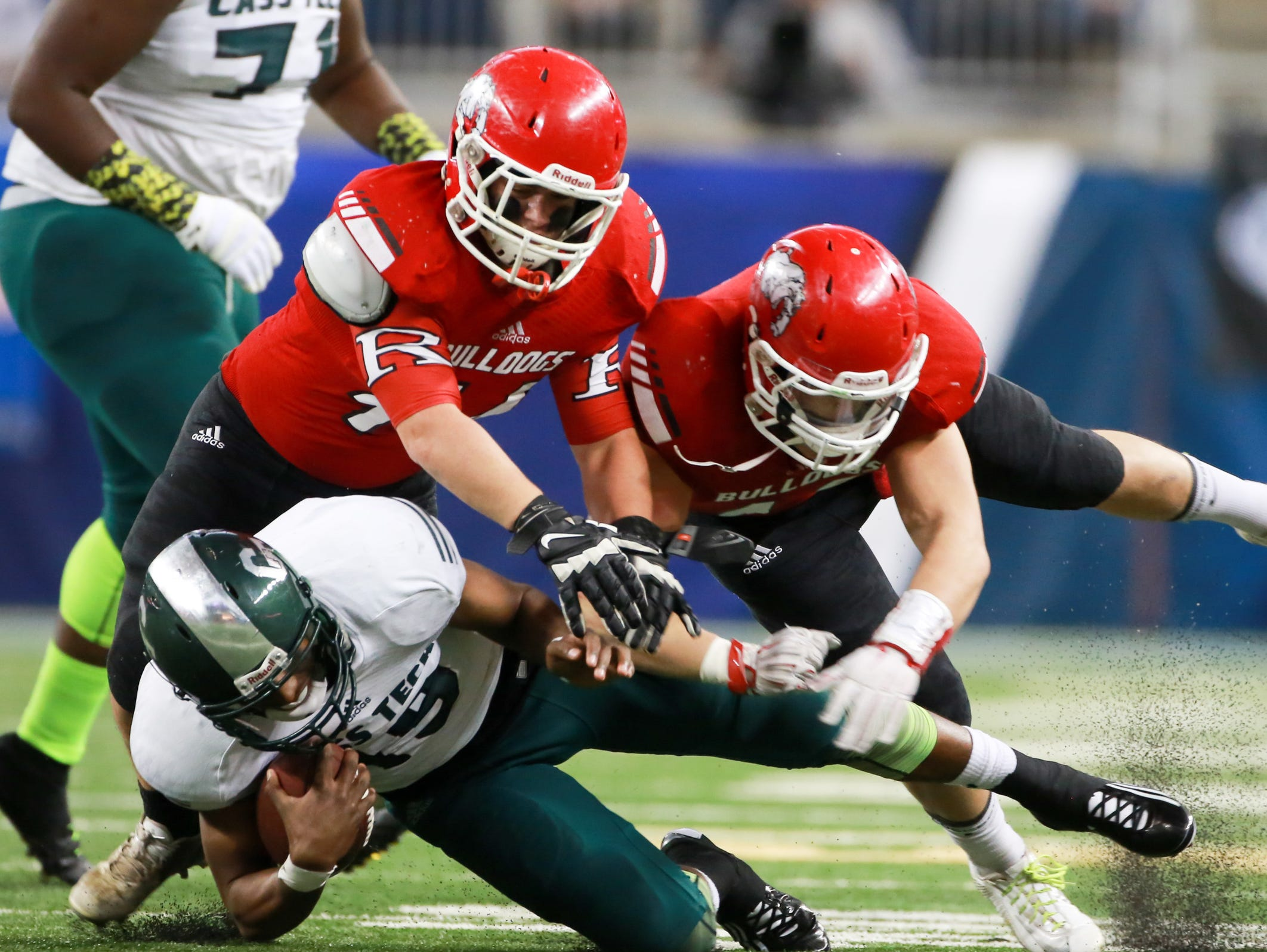 Detroit Cass Tech QB is tackled by Romeo DB Jacob Hernden and Domenico Bongiorno after gaining yards, during the first half of the Michigan High School Athletic Association football Division 1 finals at Ford Field in Detroit on Saturday, Nov. 28, 2015.