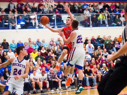 Central York's Nathan Markey goes up for the shot while Spring Grove's Liam Flaherty defends Friday at Spring Grove High School. The Panthers won, 53-50.