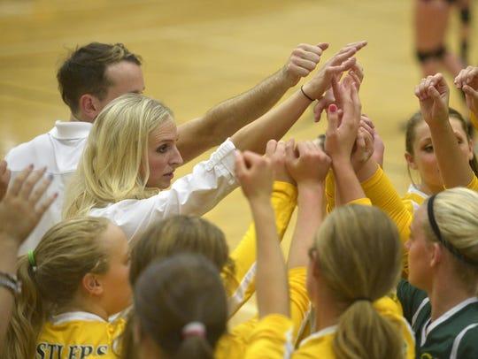 CMR head volleyball coach Theresa Besich, left, huddles